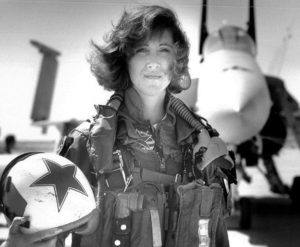 Woman standing in front of military jet in military uniform