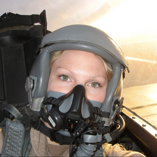Woman in military jet with helmet on