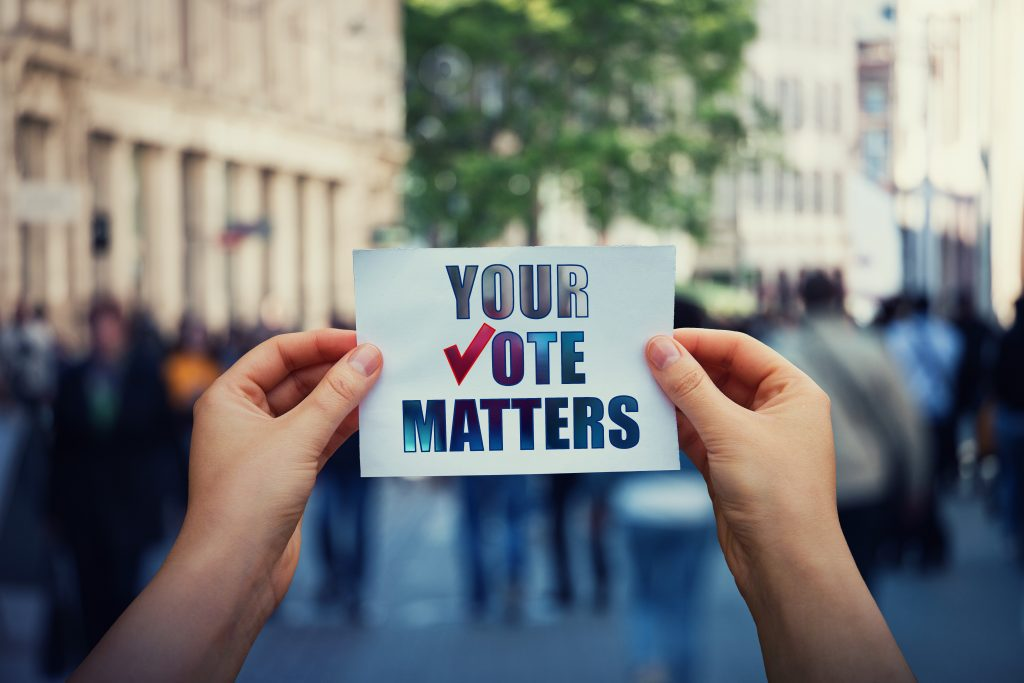 Hands hold a paper sheet with the message your vote matters over a crowded street background. People legal and democratic rights, every voice counts. Election campaign and electoral agitation concept.