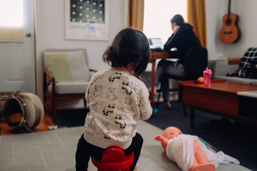 mom working in background with child playing