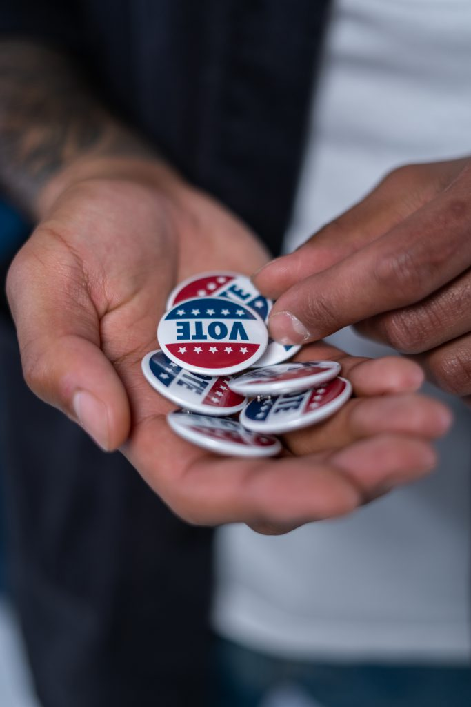 man's hands with vote buttons
