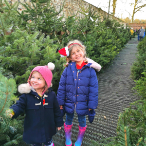 Two little girls smiling in Christmas Tree lot