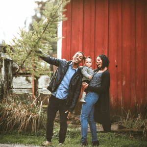Man, Woman, and toddler smiling with real Christmas Tree on a farm