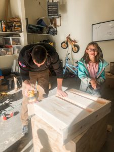 dad and daughter building with wood