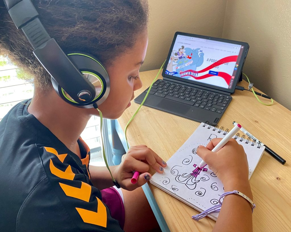 girl drawing and listening to podcast