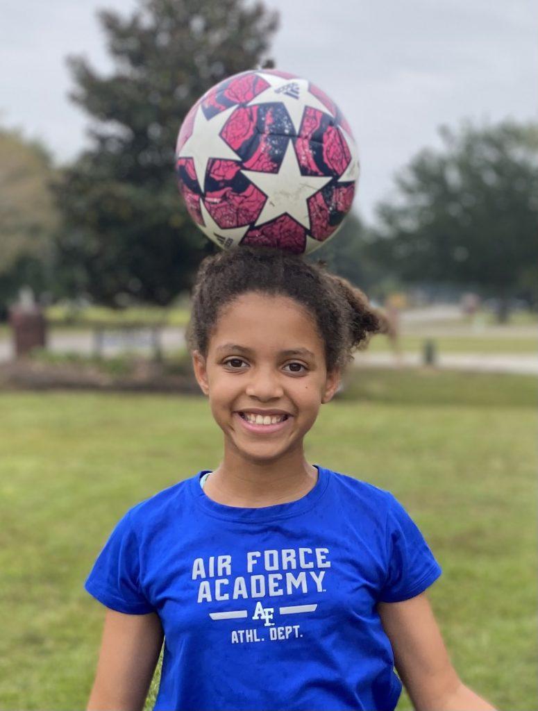 girl with soccer ball balanced on head