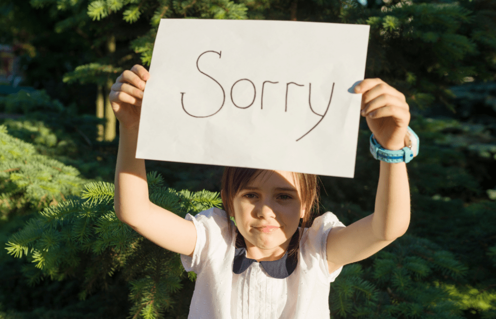 """girl holding up a sign with """"sorry"""""""