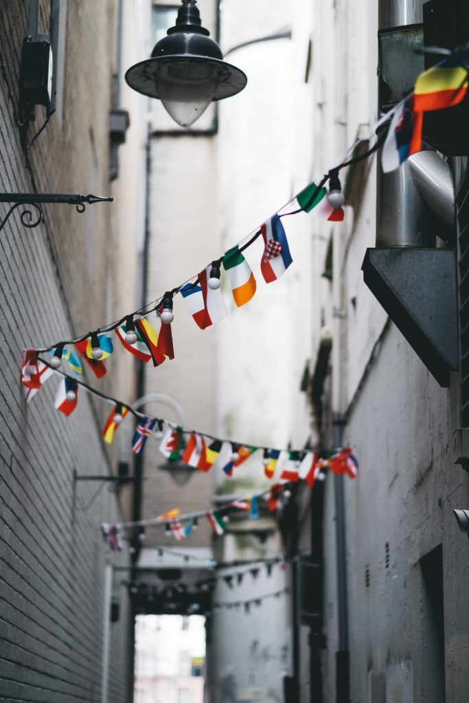 flags from multiple countries in alley