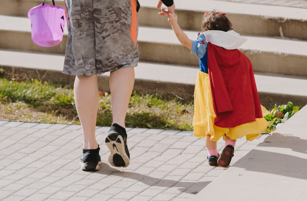 parent trick-or-treating with child in costume