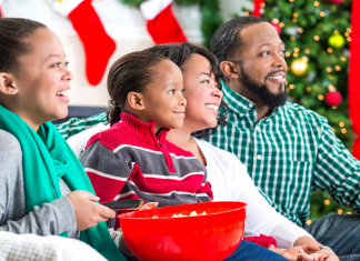 A family laughing while watching a movie together at the holidays