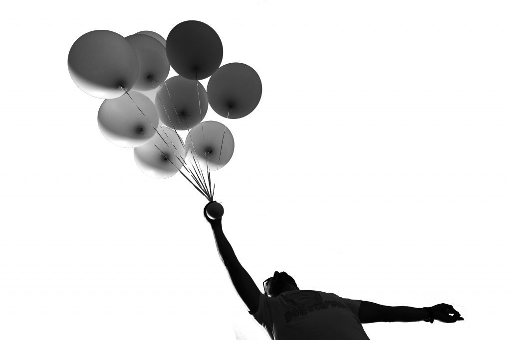 man holding balloons in black and white