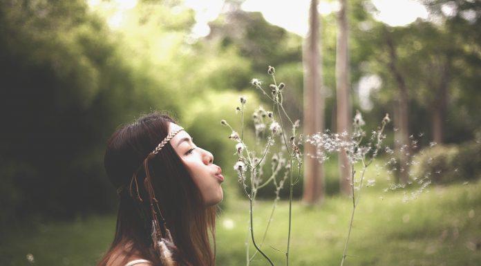 dark-haired woman blowing dandelion seeds in a field