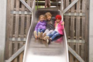 three kids on a slide on a playground