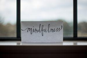 "paper with ""mindfulness"" written on it, sitting on windowsill"