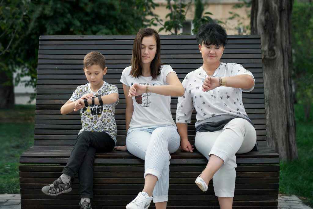 parents and child sitting on bench looking at watches