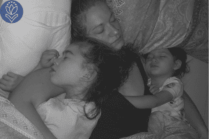 mother sleeping in bed with two daughters
