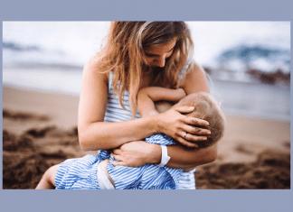 mother breastfeeding toddler on beach