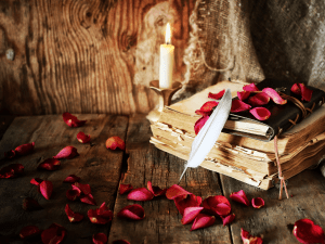 flower petals with a worn book and soft candle to indicate romance