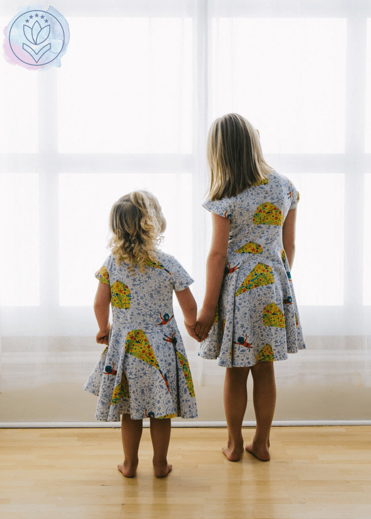 2 daughters standing at a window