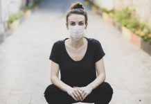 woman sitting on the ground and wearing a protective mask