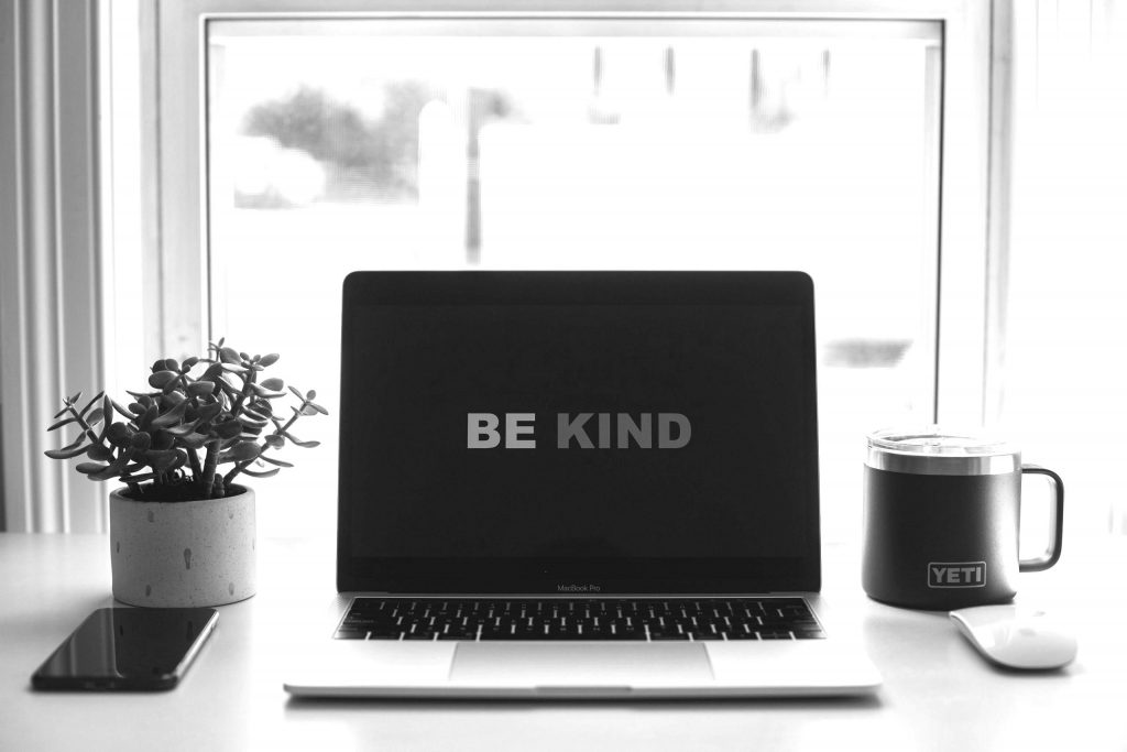 computer with be kind on screen on desk with plant and mug in black and white