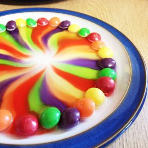 skittles on a plate with water to make a rainbow