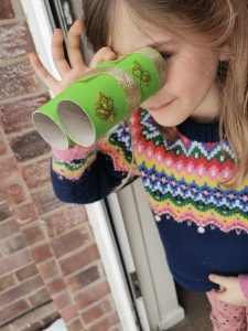 child looking through homemade binoculars