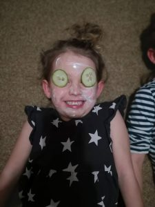 young girl with face mask and cucumbers on eyes