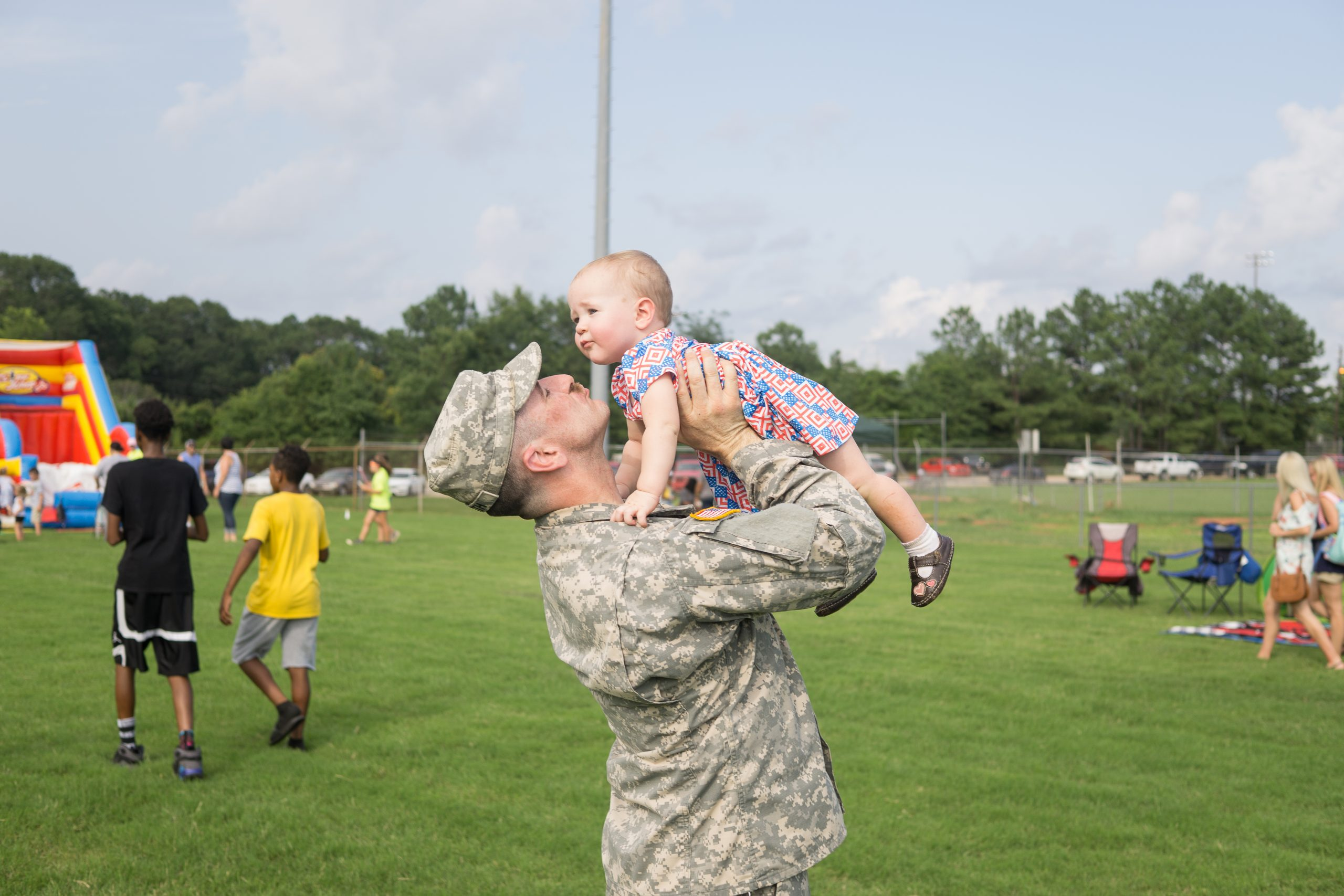 military dad holding small child