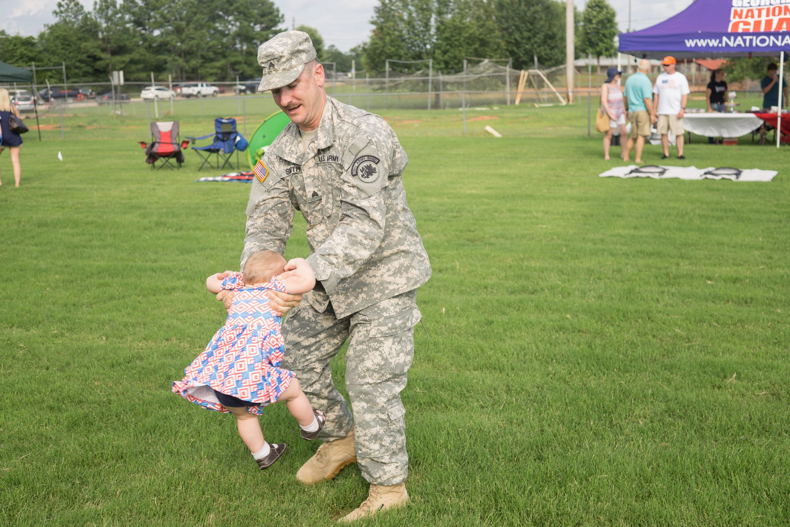 dad in military uniform swinging a small child around on grass