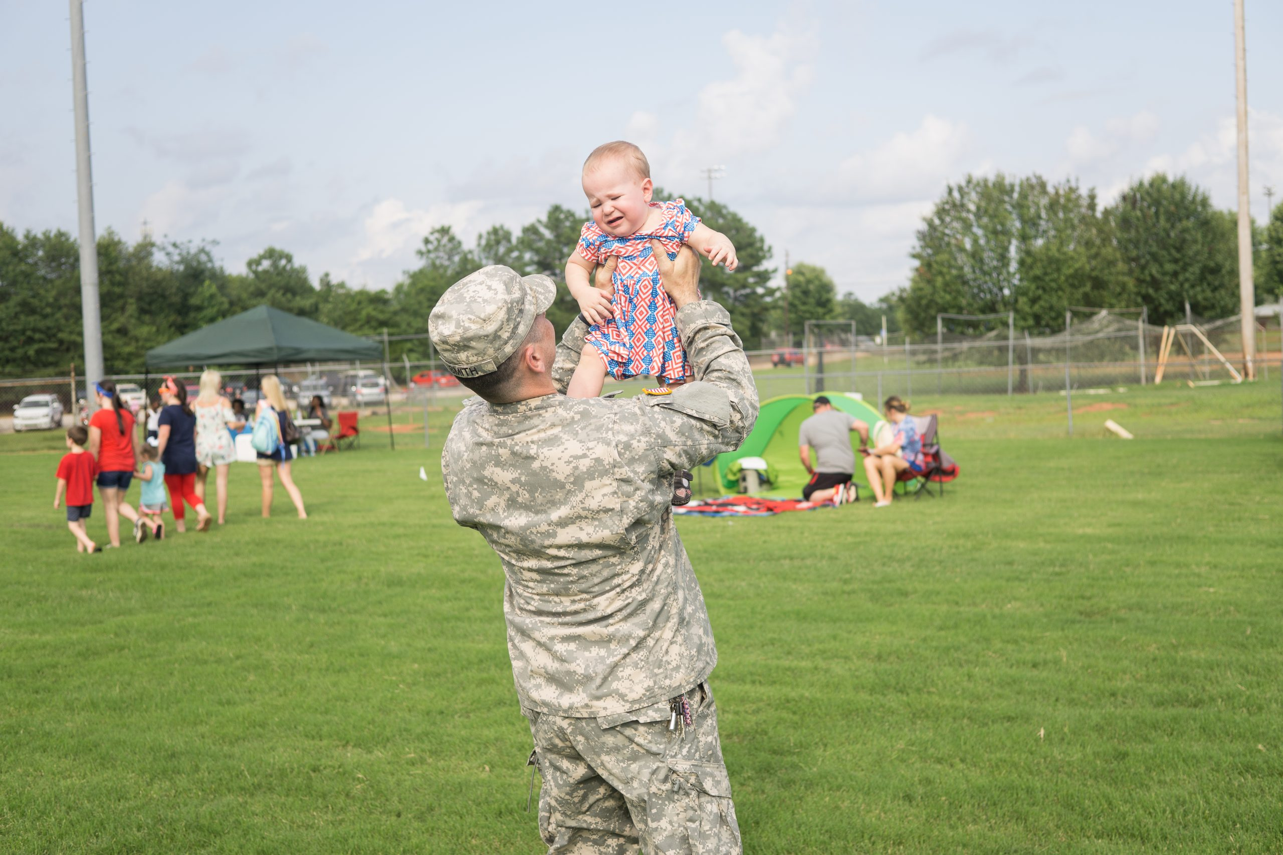military dad holding child in the air
