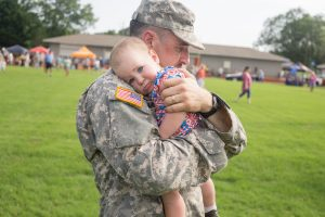 soldier holding a small child