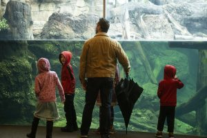 father and kids at the aquarium