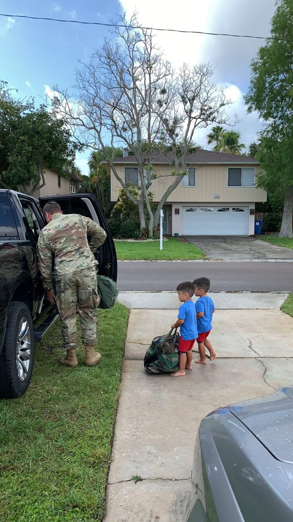military dad getting in car with sons watching