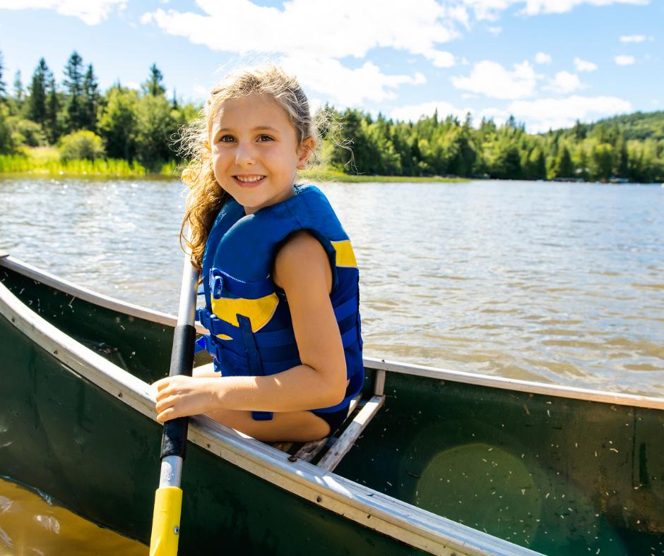 girl wearing life jacket in a canoe