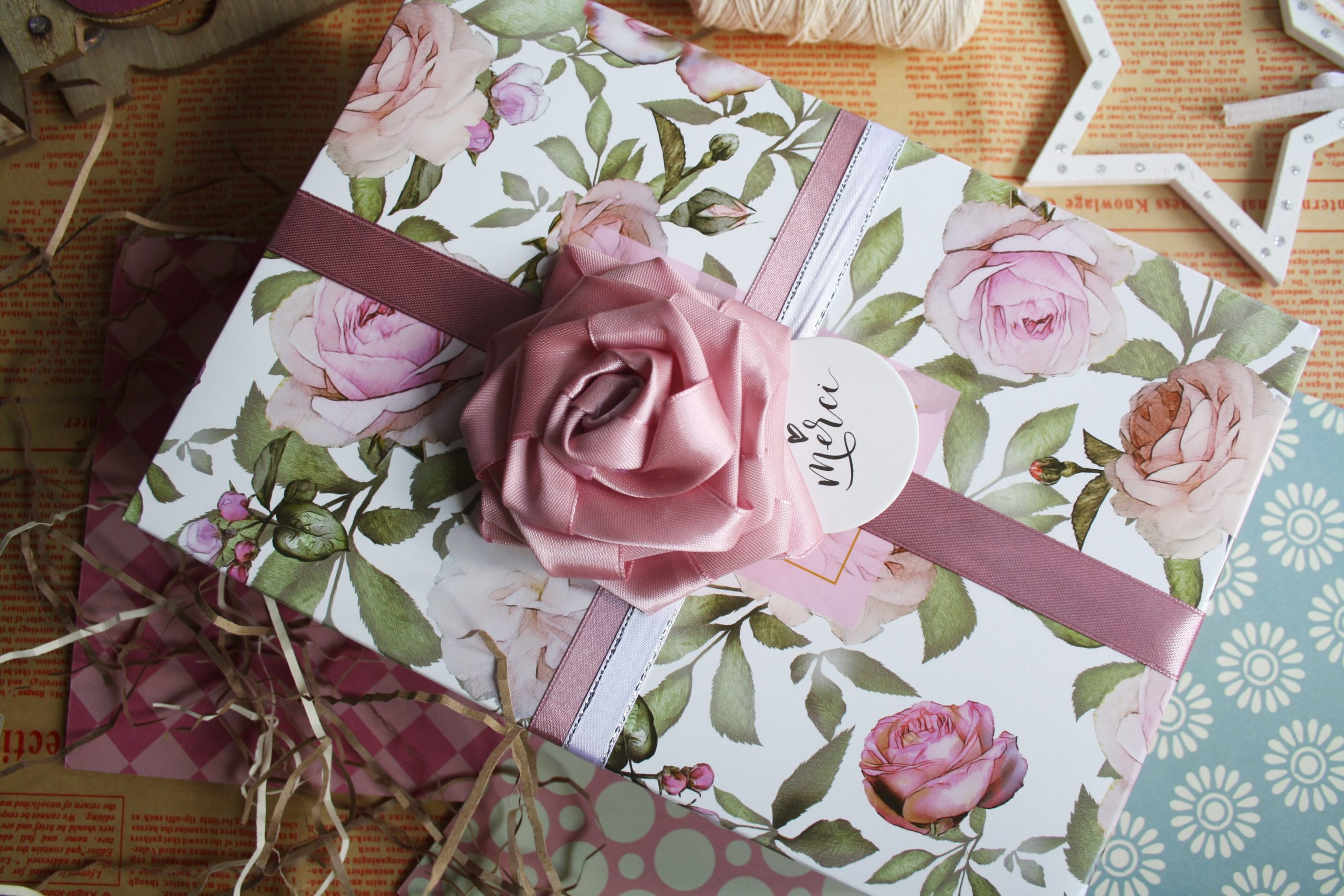 wrapped gift with pink rose bowl and wrapping papers
