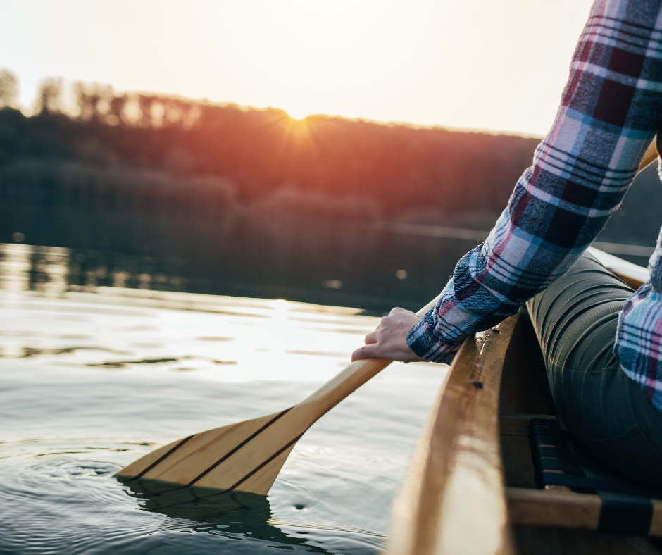 person holding a paddle on the water