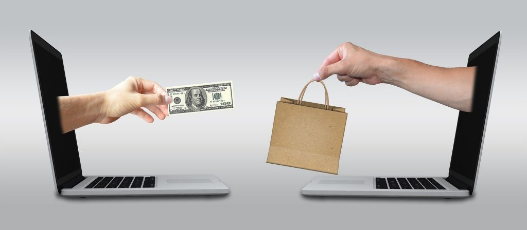 two laptops with hands reaching out, one handing cash to another handing a shopping bag