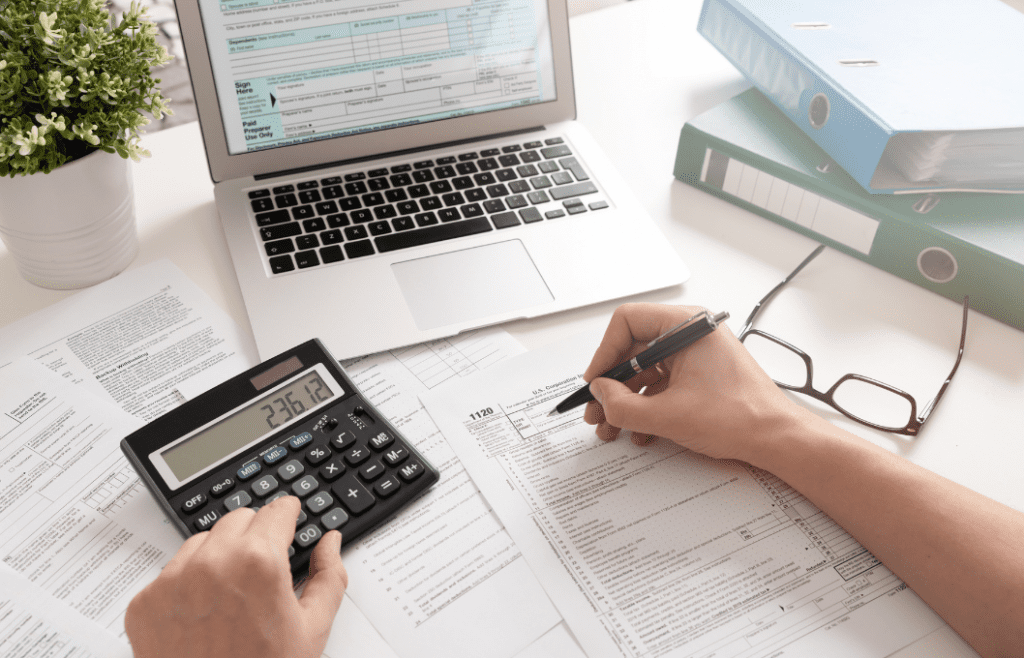 person with papers, computer, and calculator working on taxes