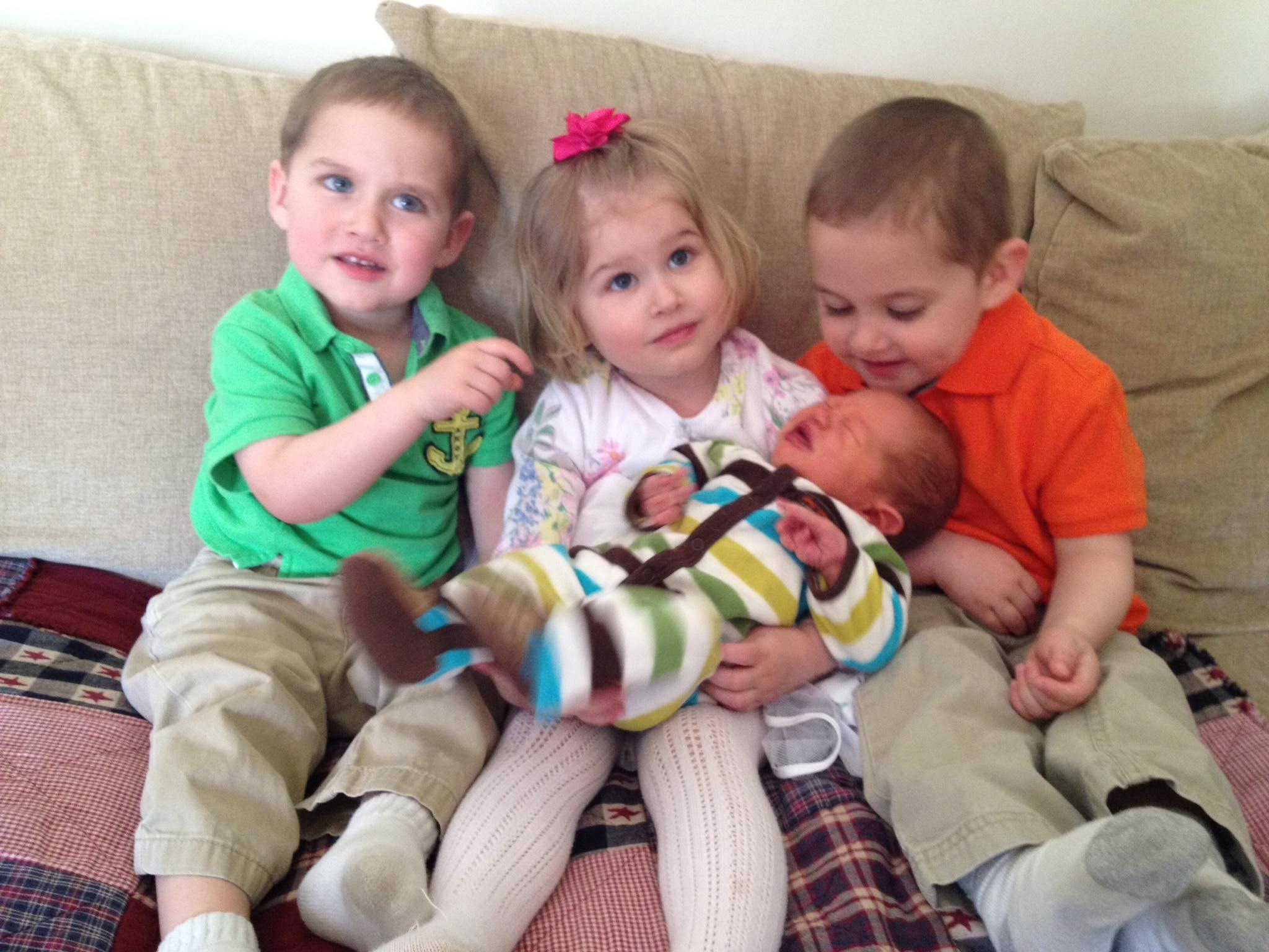 three children sitting on a couch holding a new baby
