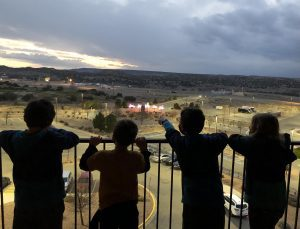 four children standing on a balcony watching the sunset