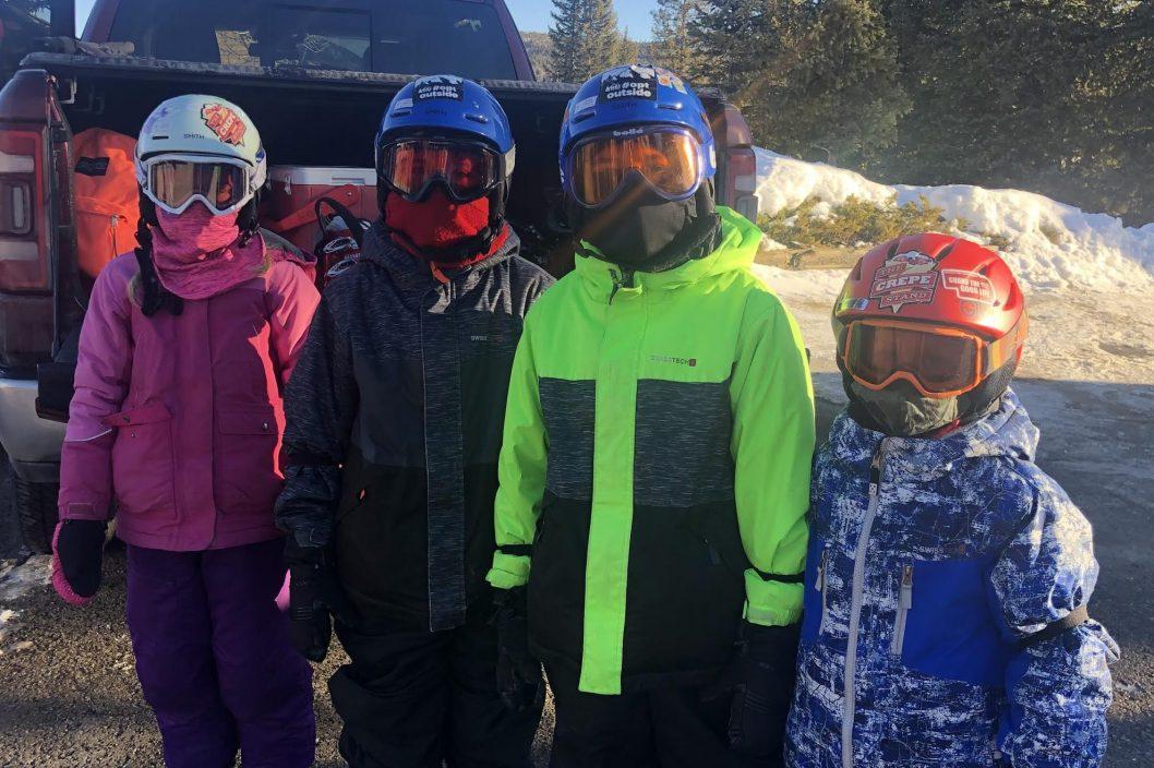 four kids standing in ski gear
