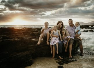 family sitting by the ocean, one child handicapped and one with down syndrome