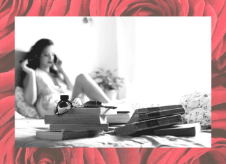 black and white photo of woman on bed in boudoir shoot with red rose background