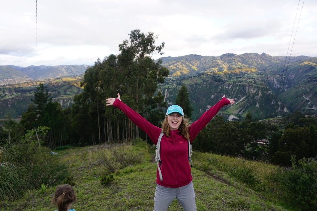 blonde woman in a red jacket and blue baseball cap standing in front of mountains