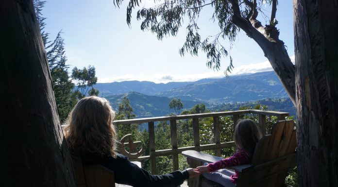 mom holding little girl's hand in porch chairs on a deck overlooking mountains