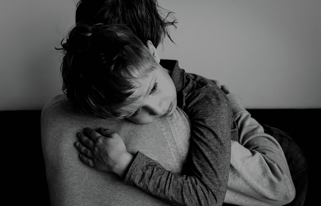 child hugging a parent in black and white