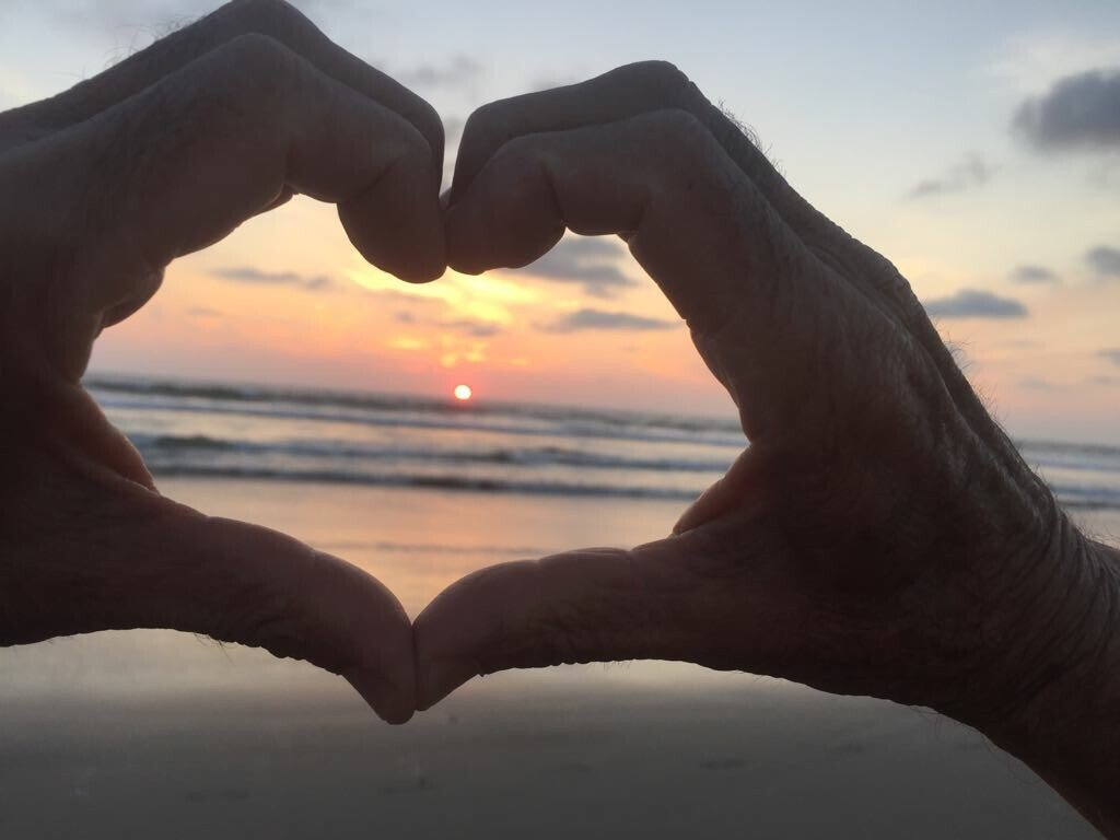 hands making a heart on the beach
