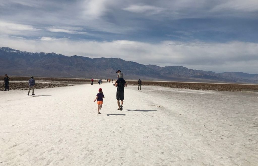A man and two kids hike across the white salt flats in Death Valley National Park