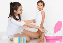 mom and toddler standing with a potty chair